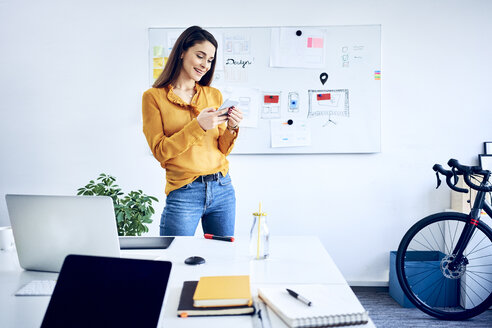 Smiling businesswoman holding smartphone at whiteboard in office - BSZF01038