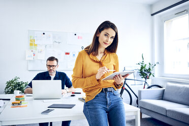 Portrait of businesswoman using tablet in office with colleague in background - BSZF01041