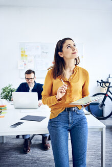 Businesswoman holding tablet in office with colleague in background - BSZF01044