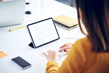 Close-up of businesswoman using tablet at desk in office - BSZF01047