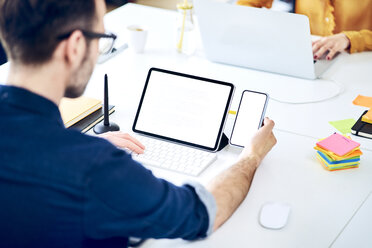 Businessman working on smartphone and tablet at desk in office - BSZF01050