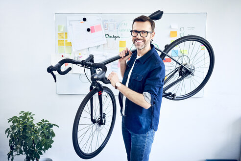Portrait of smiling businessman carrying bicycle in office - BSZF01059