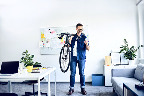 Smiling businessman carrying bicycle in office looking at smartphone - BSZF01062