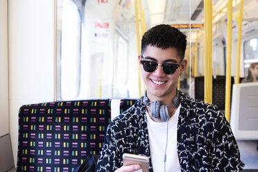 Young man using smartphone inside train - IGGF00879