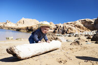 Spain, Menorca, toddler playing with deadwood on the beach - IGGF00897