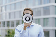 Young businessman standing in front of modern office building, using megaphone - KNSF05577