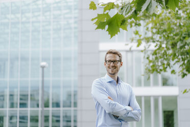Young businessman standing in front of modern office building, with arms crossed - KNSF05580