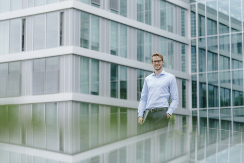 Young businessman standing in front of modern office building, carrying laptop - KNSF05583