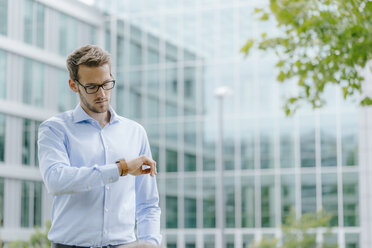 Young businessman standing in front of modern office building, checking the time - KNSF05586