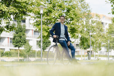 Young businessman in park, leaning on his bicycle - KNSF05595