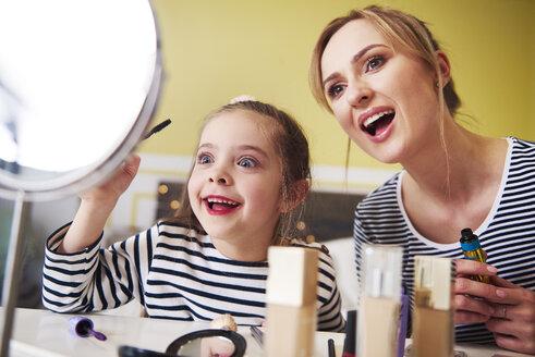 Mother and daughter applying make up together - ABIF01203
