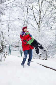 Smiling mother carrying happy son at snow covered park - ASTF04774