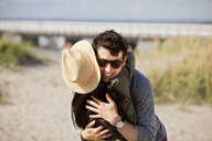 Happy young man embracing female friend at beach on sunny day - ASTF04907