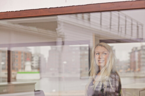 Happy thoughtful businesswoman in creative office seen through window - ASTF04943