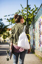Rear view of woman with skateboard and purse standing on sidewalk - ASTF04964