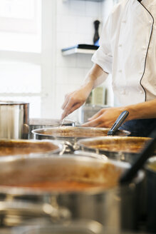 Midsection of male chef stirring gravy in utensil at commercial kitchen - ASTF04985