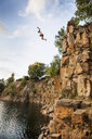 Low angle view of man jumping in lake against sky - ASTF05009