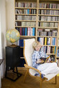 Boy reading book while sitting on lounge chair against bookshelf at home - ASTF05021