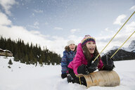 Girls sledding in snowy field - HEROF24511