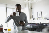 Man sipping morning coffee and texting in kitchen - HEROF24529