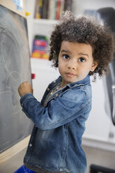Girl with curly hair drawing at blackboard - HEROF24544