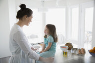 Mother and daughter in pajamas in morning kitchen - HEROF24547