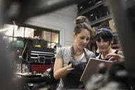 Female motorcycle mechanics with digital tablet working in auto repair shop - HEROF24622