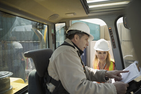 Female foreman with clipboard and forklift driver talking in industrial container yard - HEROF24652