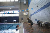 Female coach talking to swimmers in swimming pool at practice - HEROF24664