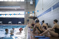 Female coach explaining stroke to swimmers in swimming pool at practice - HEROF24667