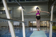 Girl swimmer standing at the edge of springboard diving board over swimming pool - HEROF24670