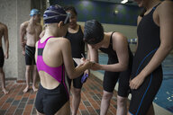 Female swimmer signing autograph for girl at swimming pool - HEROF24676