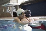 Female swimmers hugging in swimming pool - HEROF24682