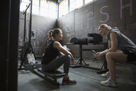 Fit women resting, weightlifting and talking in gritty gym - HEROF24688