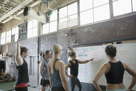 Female instructor and crossfit students at whiteboard in gritty gym - HEROF24697