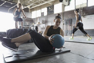 Focused, strong woman doing seated medicine ball twist in gritty gym - HEROF24703