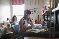 Female college student with headphones studying at laptop in dorm room - HEROF24715