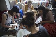 Female college students studying on floor in dorm room - HEROF24724