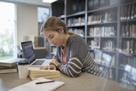 Focused female college student studying, reading book in library - HEROF24766