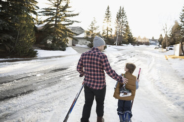 Father and son walking with ice hockey sticks and ice skates on snowy road - HEROF24787