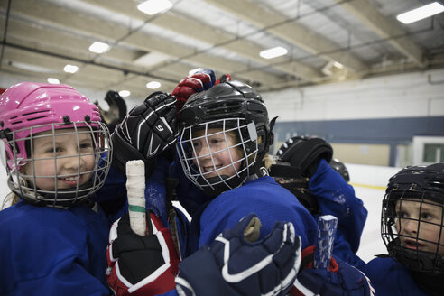 Girl and boy ice hockey players celebrating on ice hockey rink - HEROF24790