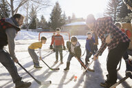 Fathers and sons playing ice hockey in sunny, snowy driveway - HEROF24793