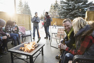 Families drinking beer at fire pit and playing ice hockey in snowy driveway - HEROF24796