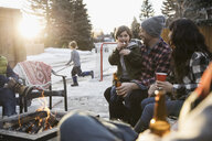 Family roasting marshmallows and drinking beer at fire pit in snowy driveway - HEROF24799