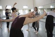 Female ballet dancer practicing back bend in dance studio - HEROF24829