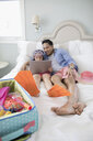 Father and daughter wearing flippers packing for vacation, using digital tablet on bed - HEROF24898