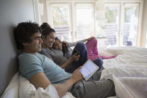 Family relaxing, using digital tablet on bed - HEROF24934