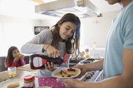 Father and daughter pouring maple syrup on pancakes in kitchen - HEROF24937