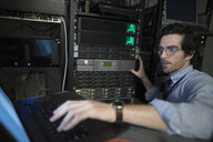 Focused technician with laptop working at server panel in server room - HEROF24988