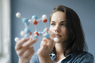 Female scientist studying molecule model, looking for solutions - KNSF05643